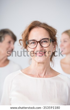 Portrait of smiling mature woman in glasses with family - stock photo