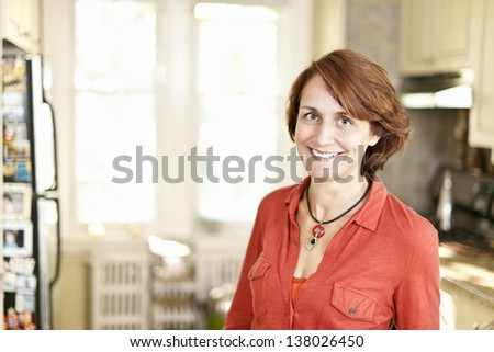 Portrait of smiling mature woman in kitchen at home - stock photo