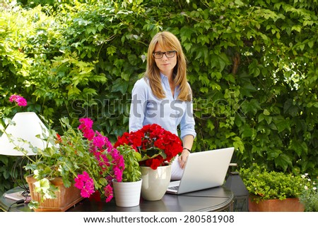 Portrait of smiling mature woman standing and working at laptop a small flower shop. Small business owner. - stock photo