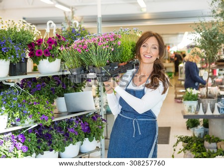 Portrait of smiling mid adult botanist carrying crate full of flower plants in shop - stock photo