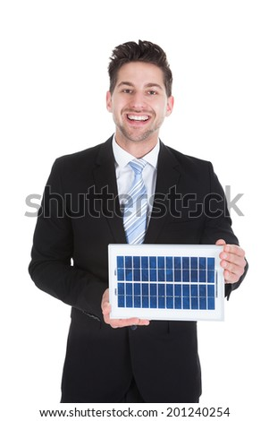 Portrait of smiling mid adult businessman holding solar panel over white background - stock photo