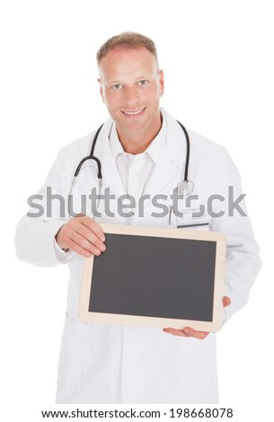 Portrait of smiling mid adult male doctor holding blank slate over white background