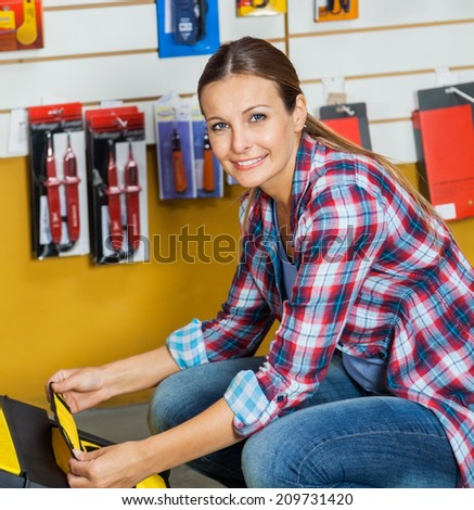 Portrait of smiling mid adult woman analyzing tool case in hardware store - stock photo
