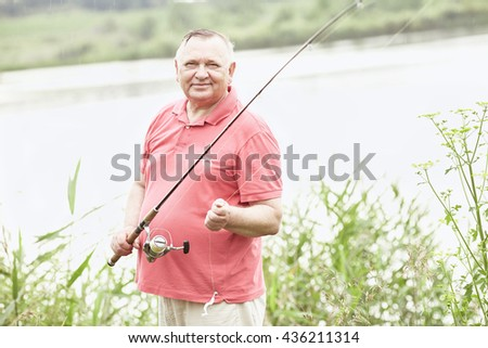 Portrait of smiling middle aged man wearing polo shirt, angling with rod and spinning reel in rain on summer lake - fishing concept - stock photo