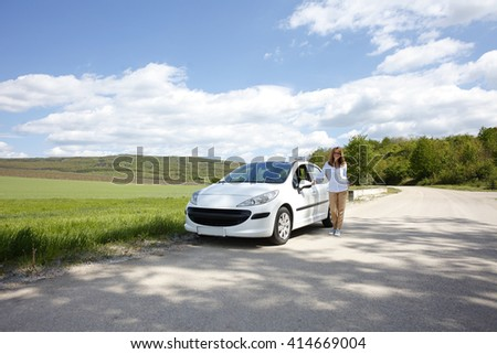 Portrait of smiling middle aged woman standing on the side of the road besides her broken down car.  - stock photo