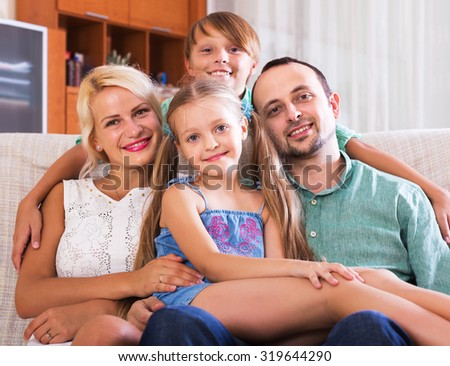 Portrait of smiling middle class caucasian family at home interior. Focus on girl