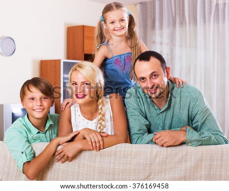 Portrait of smiling middle class caucasian family with two children at home. Focus on woman