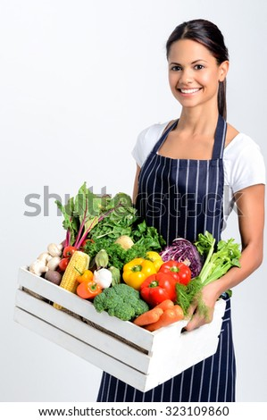 Portrait of smiling mixed race woman chef holding a crate full of fresh organic vegetables on grey background, promoting eating seasonally and sourcing from local producers - stock photo