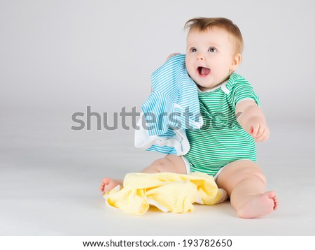 Portrait of smiling 10 months baby girl choosing clothes - stock photo