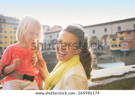 Portrait of smiling mother and baby girl eating ice cream near ponte vecchio in florence, italy - stock photo
