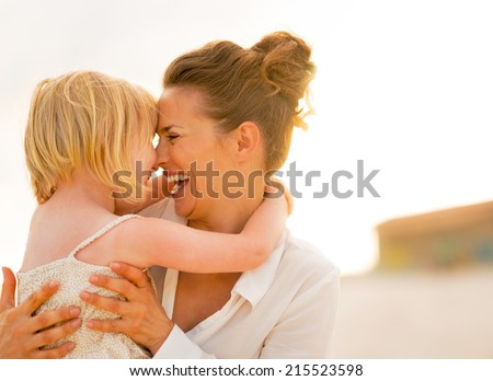Portrait of smiling mother and baby girl hugging on the beach in the evening - stock photo