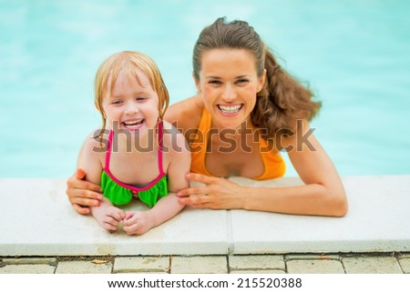 Portrait of smiling mother and baby girl in swimming pool - stock photo