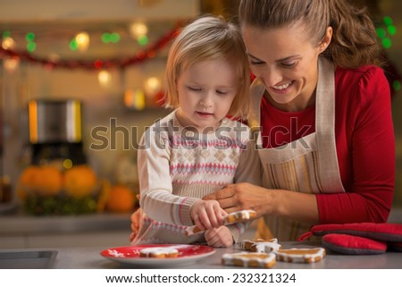Portrait of smiling mother and baby making christmas cookies - stock photo