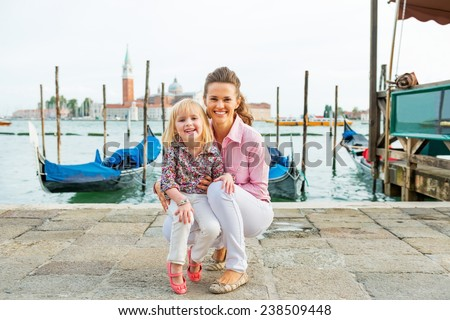 Portrait of smiling mother and baby on grand canal embankment in venice, italy - stock photo