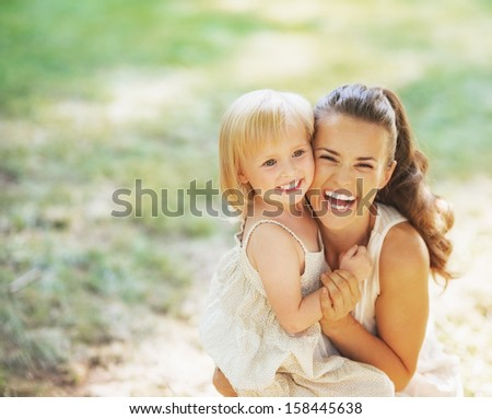 Portrait of smiling mother and baby outdoors - stock photo