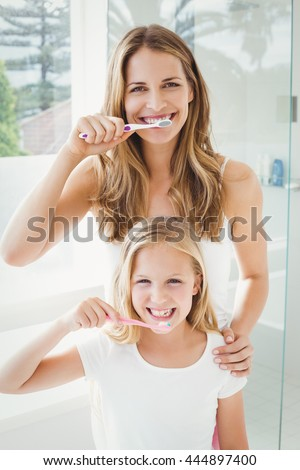 Portrait of smiling mother and daughter brushing teeth at home - stock photo