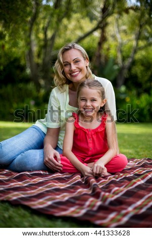 Portrait of smiling mother and daughter sitting on blanket in yard - stock photo