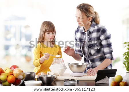 Portrait of smiling mother and her adorable daughter baking cookies together at home.