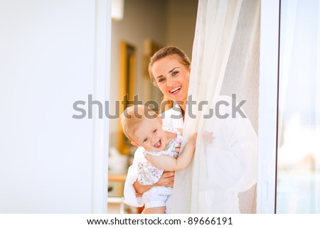 Portrait of smiling mother in bathrobe with baby looking out from window - stock photo