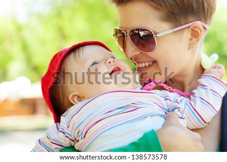 Portrait of smiling mother with baby. Focused on baby - stock photo