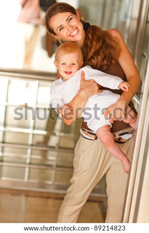 Portrait of smiling mother with baby looking out from elevator - stock photo