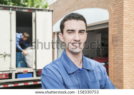 Portrait of smiling mover with moving truck in the background