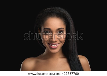 Portrait of smiling mulatto woman on dark background. Attractive, satisfied, cheerful african american girl - stock photo