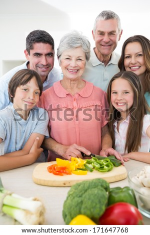 Portrait of smiling multi-generation family preparing food at kitchen counter - stock photo