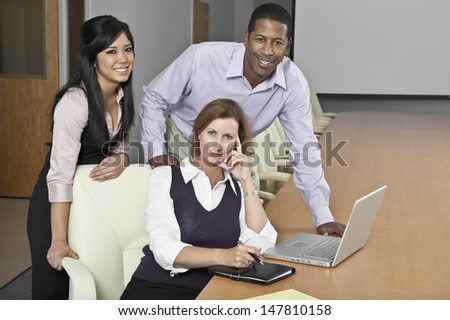 Portrait of smiling multiethnic businesspeople with laptop in conference room - stock photo