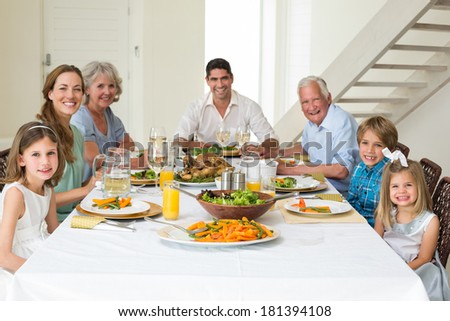 Portrait of smiling multigeneration family having meal together at dining table - stock photo
