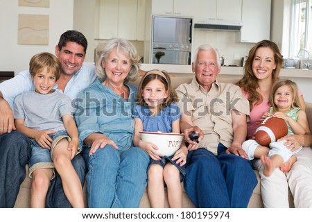 Portrait of smiling multigeneration family spending leisure time together at home - stock photo