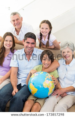 Portrait of smiling multigeneration family with globe at home - stock photo