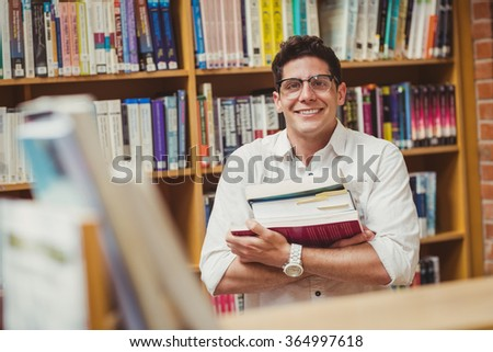 Portrait of smiling nerd holding books in library