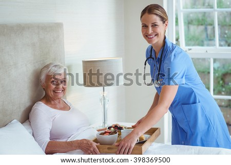 Portrait of smiling nurse giving food to senior woman at home - stock photo
