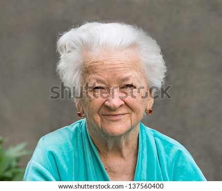 Portrait of smiling old woman on a gray background
