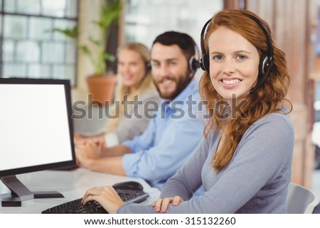 Portrait of smiling operators working while sitting in office