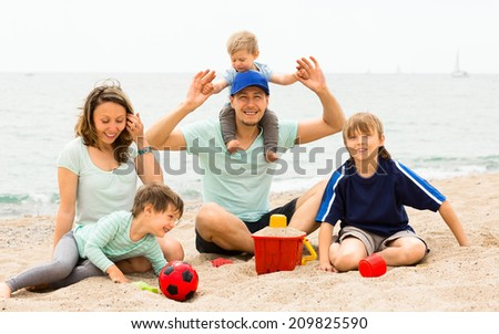 Portrait of smiling parents and their children on  sand by sea - stock photo