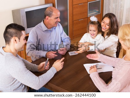 Portrait of smiling parents and their children playing cards together and keeping score indoor - stock photo