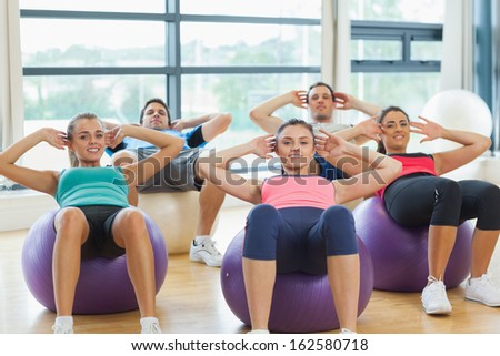 Portrait of smiling people doing abdominal crunches on fitness balls in the bright gym - stock photo
