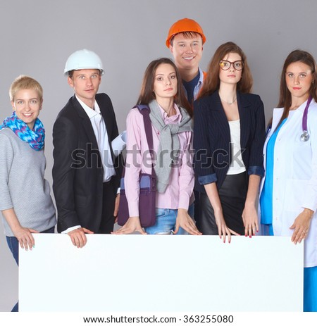 Portrait of smiling people with various occupations holding blank billboard  - stock photo