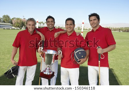 Portrait of smiling polo team with trophy on field - stock photo