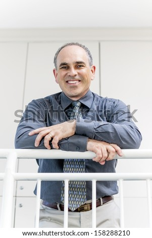 Portrait of smiling proud business man standing in office hallway leaning on railing - stock photo