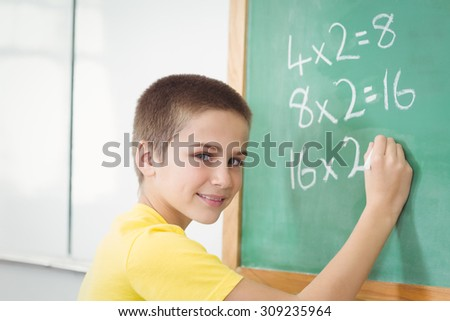 Portrait of smiling pupil calculating on chalkboard in a classroom in school - stock photo