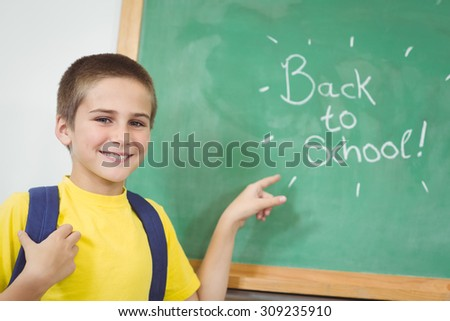 Portrait of smiling pupil pointing on back to school sign on chalkboard in school - stock photo