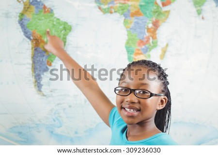 Portrait of smiling pupil pointing on world map in a classroom in school
