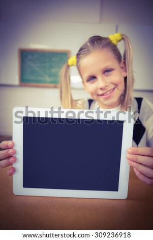 Portrait of smiling pupil showing tablet to camera in a classroom - stock photo