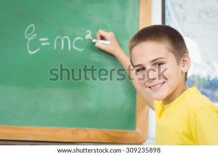 Portrait of smiling pupil writing on chalkboard in a classroom in school - stock photo