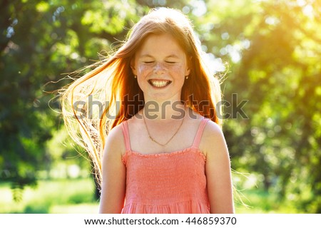 Portrait of smiling redhead girl with freckles in summer sun - stock photo