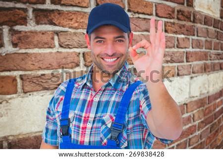 Portrait of smiling repairman gesturing okay against red brick wall - stock photo