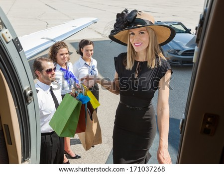 Portrait of smiling rich woman with shopping bags boarding private jet while pilot and airhostess looking at her - stock photo